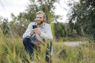Smiling man using smartphone in nature - KNSF03668
