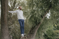 Man standing on tree trunk looking at distance - KNSF03671