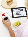 Woman using digital tablet while eating breakfast - FOLF08631