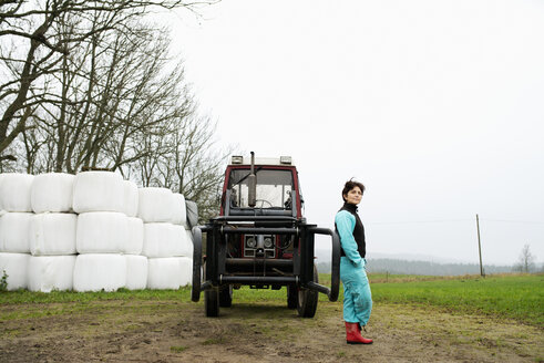 Portrait of farmer leaning against tractor - FOLF08817
