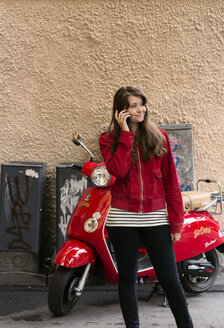 Young woman with red motorbike and mobile phone, standing by building wall - FOLF08925