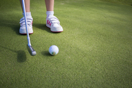 Low-section shot of girl about to swing golf ball off artificial turf - FOLF08949