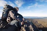 Successful male hiker sitting on mountain - CAVF33958