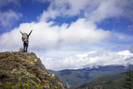 Low angle view of woman standing with arms raised on mountain against cloudy sky - CAVF33985