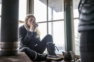 Woman sitting on window and drinking coffee in cottage - CAVF33991