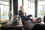Kettle on table by woman relaxing on window in cottage - CAVF33994