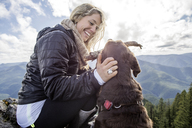 Low angle view of happy woman playing with dog on mountain cliff - CAVF34000
