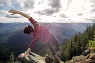 Woman bending with arms outstretched on rock at mountain cliff against sky - CAVF34003