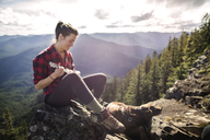 Woman sitting with dog on rock and playing ukelele at mountain cliff - CAVF34006
