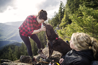 Women enjoying with dog on mountain cliff against sky - CAVF34009