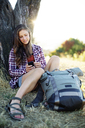 Young woman using mobile phone while sitting with backpack on grassy field - CAVF34084