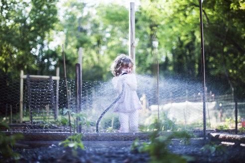 Playful girl playing with water in yard - CAVF34165