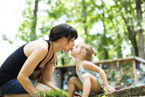 Loving daughter kissing mother on mouth while sitting in backyard - CAVF34171