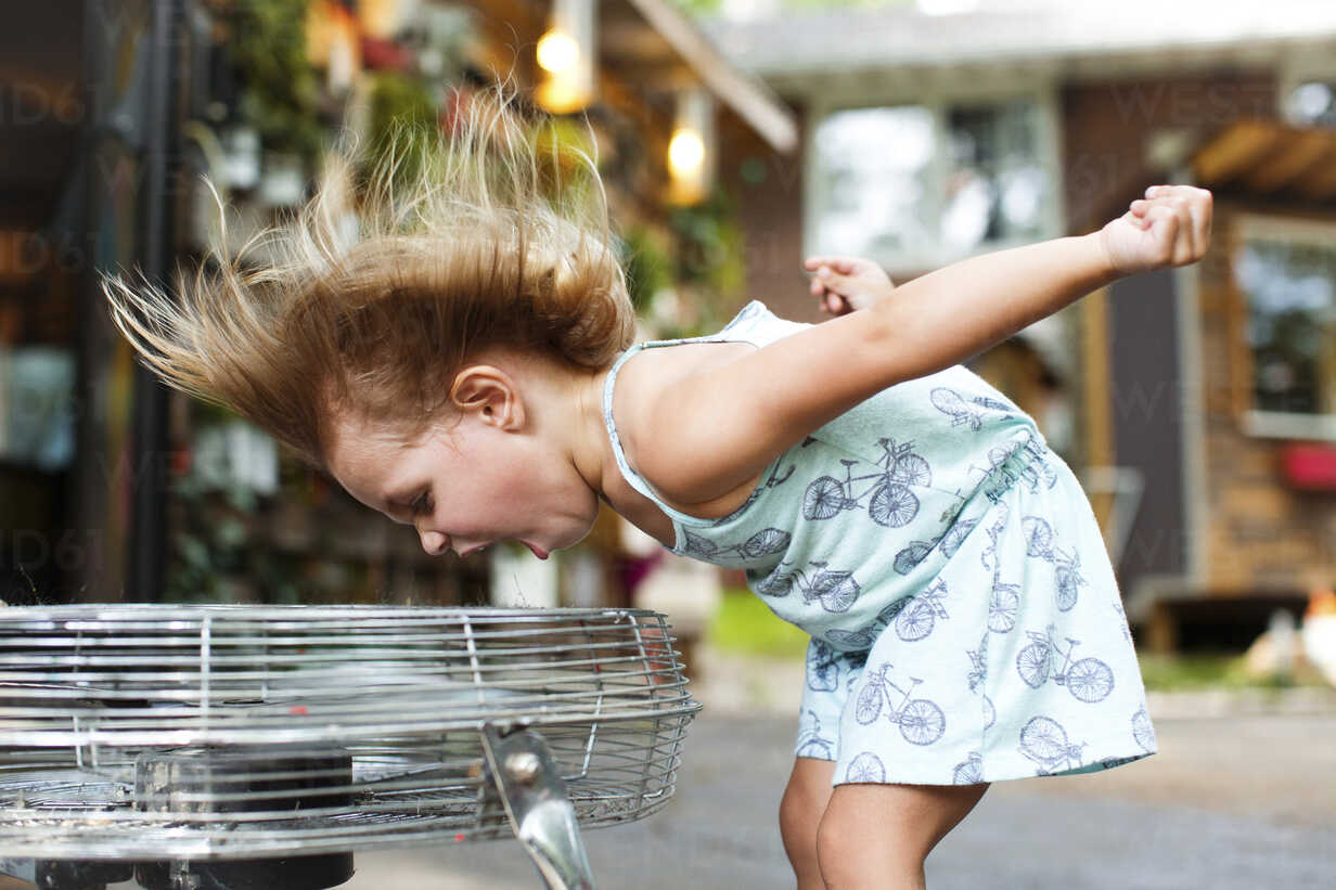 Girl screaming while enjoying breeze from electric fan - CAVF34174 - Cavan Images/Westend61