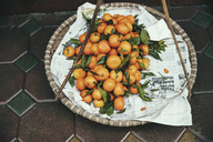 High angle view of oranges in basket on sidewalk - CAVF34207