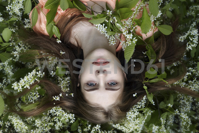 Overhead portrait of woman relaxing on plants at yard - CAVF34247