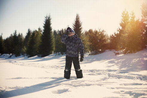 Boy standing on snow covered field against sky during sunset - CAVF34253