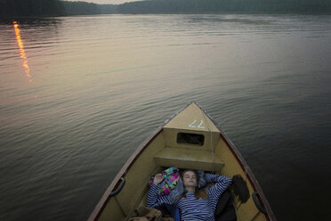 High angle view of woman sleeping while traveling in boat on river during sunset - CAVF34277