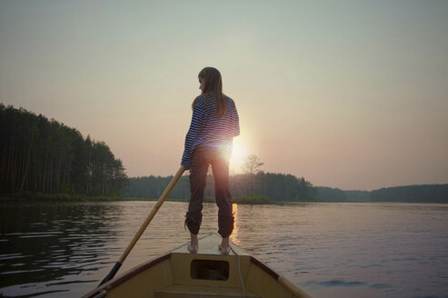 Rear view of woman canoeing while standing on ship's bow against clear sky during dusk - CAVF34286
