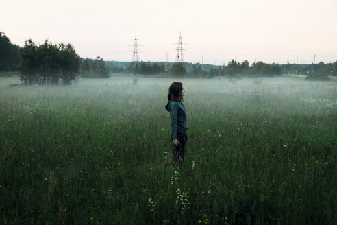 Side view of woman standing on grassy field against clear sky during foggy weather - CAVF34319