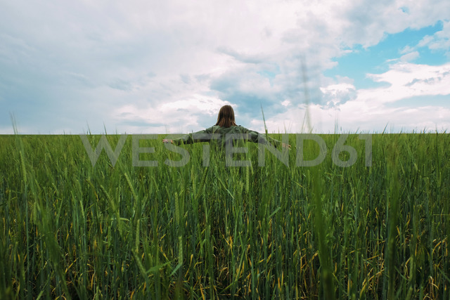 Rear view of woman with arms outstretched standing on grassy field against cloudy sky - CAVF34334