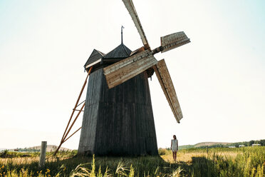 Woman standing by traditional windmill on field against clear sky - CAVF34337