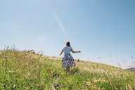 Rear view of woman on grassy field against sky during summer - CAVF34343