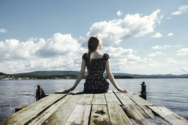 Thoughtful woman sitting on pier over river against cloudy sky - CAVF34349