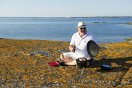Mature man grilling sausage on rocky beach - FOLF09224