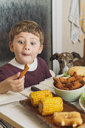 Boy with dog enjoying american food at dining table at home - SKCF00393