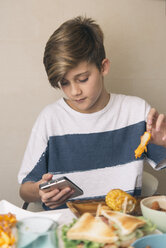 Boy eating at dining table and looking at the phone at the same time - SKCF00396