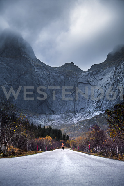 Norway, Lofoten Islands, man standing on empty road surrounded by rock face - WVF00943