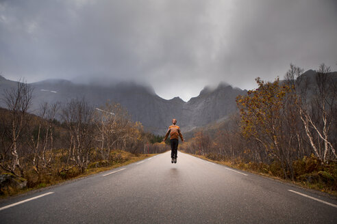 Norway, Lofoten Islands, man jumping on empty road surrounded by rock face - WVF00946