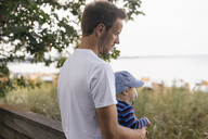 Germany, Timmendorfer Strand, father holding his son - KNSF03694