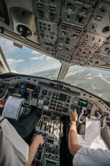 Tilt image of pilots flying airplane over landscape - MASF00004