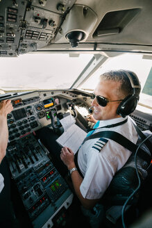 Confident smiling pilot with documents sitting in cockpit - MASF00007