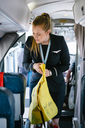 Air stewardess holding life jacket while standing in passenger cabin - MASF00010