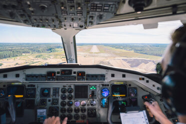 Cropped image of pilot flying airplane using control panel over landscape - MASF00013