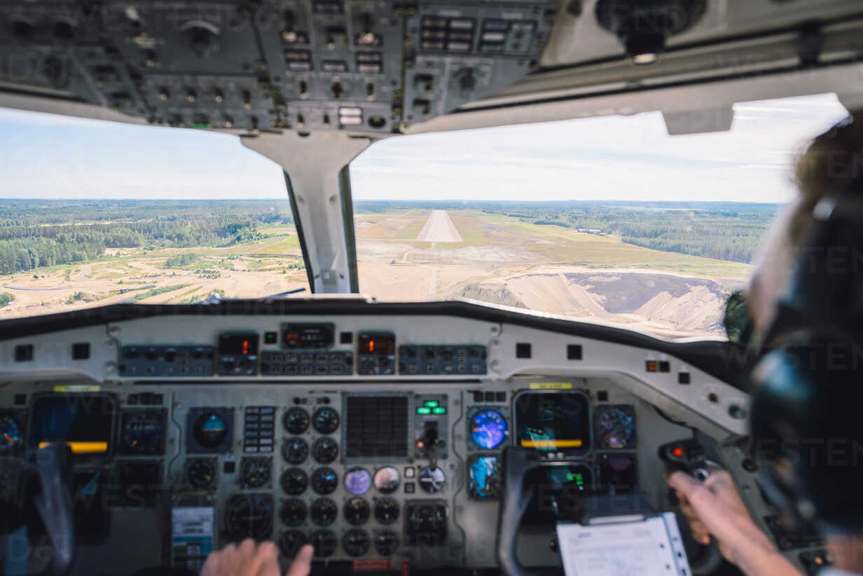 Cropped image of pilot flying airplane using control panel over landscape - MASF00013 - Helena Wahlman/Westend61