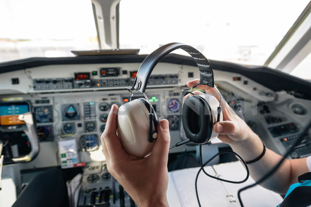 Cropped image of pilot holding ear muff while sitting in airplane - MASF00016 - Helena Wahlman/Westend61