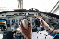 Cropped image of pilot holding ear muff while sitting in airplane - MASF00016