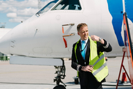 Pilot wearing reflective jacket while standing by airplane at airport - MASF00019
