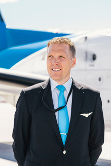 Thoughtful smiling pilot standing against airplane at airport on sunny day - MASF00022