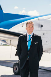 Confident pilot looking away while standing by airplane at airport on sunny day - MASF00025