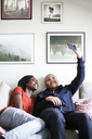 Mother and son taking selfie using mobile phone on sofa at home - MASF00028