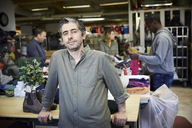 Portrait of confident mature man standing against colleagues working in warehouse - MASF00034