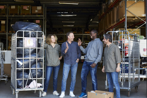 Full length of cheerful coworkers standing amidst carts at warehouse doorway - MASF00049