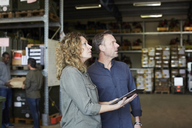 Mature colleagues looking away while holding digital tablet at warehouse - MASF00052