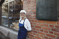 Portrait of smiling senior baker leaning on brick wall outside bakery - MASF00076