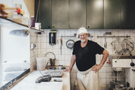 Portrait of senior baker standing by kitchen counter in bakery - MASF00082